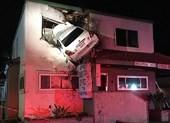 Tai nạn hy hữu: Xe treo lơ lửng trên mái nhà