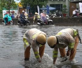 CSGT lội nước giúp người dân khơi miệng cống chống ngập