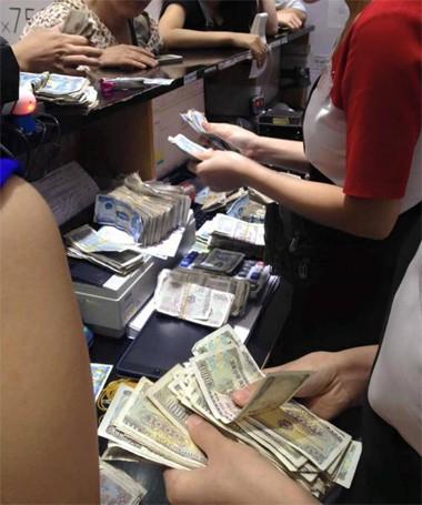 Nhân viên cửa hàng đếm tiền của chị Hằng.