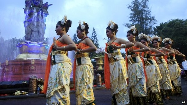 Women in traditional costumes danced during a parade for 2013's last sundown on Bali, Indonesia