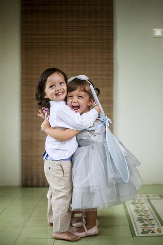 """Ngay sau đó, """"cô Bống"""" tiếp tục chia sẻ hình ảnh hiện tại vô cùng đáng yêu của hai bé Tôm và Tép ôm nhau cười tươi hạnh phúc. Trong hình, bé Tôm - Aiden (trái) mặc áo sơ mi kết hợp với quần kaki, bé Tép - Lea (phải) mặc váy công chúa màu xanh, ton-sur-ton với bờm tóc và phụ kiện cánh bướm đeo ở vai. Dù sinh đôi song Tôm và Tép có nhiều điểm khác nhau. Tôm có mái tóc đen nâu, còn cô Tép lại có mái tóc nâu vàng. Tuy nhiên, cả hai đều sở hữu đôi mắt đẹp và nụ cười rạng rỡ như thiên thần."""