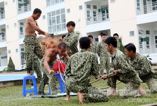 Một chiến sĩ đặc công thể hiện khả năng phi thường, khi cổ họng ghì cong 3 cây đao nhọn, vai kê gạch để đồng đội công phá.