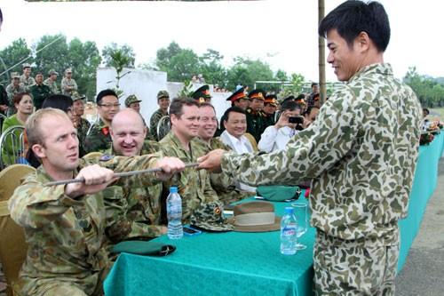 Khách tham quan đến từ Lực lượng đặc biệt của quân đội Australia kiểm tra độ cứng của một thanh sắt phi 14...