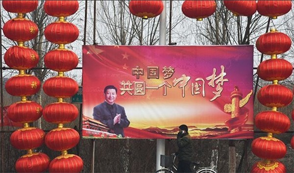 n walks past a billboard featuring a photo of Chinese President Xi Jinping beside lantern decorations for the Lunar New Year in Baoding, China's northern Hebei province. The Chinese characters read