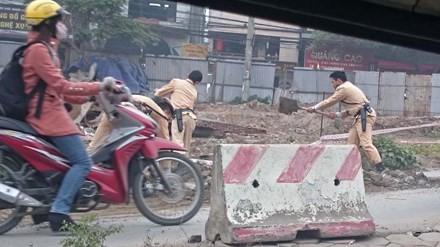 Các chiến sĩ CSGT dùng xẻng xúc đất đá rơi ra lòng đường. Ảnh: Minh Anh.