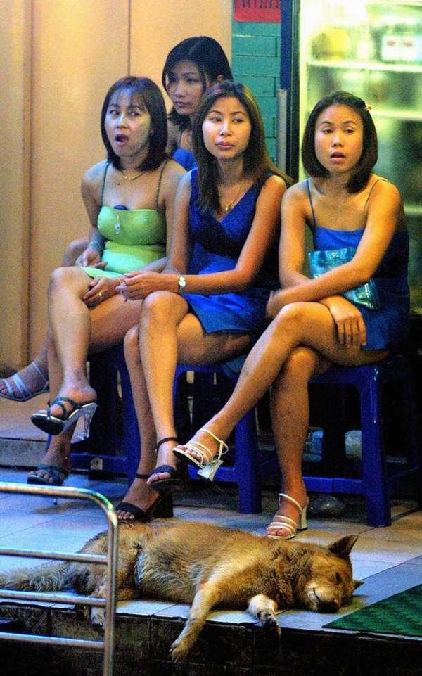 Các cô gái trẻ hành nghề mại dâm ngồi đợi khách ngoài quán bar tại phố đèn đỏ ở Bangkok.