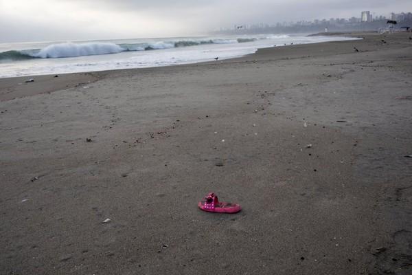 Ngày 16-2, một nam du khách thích thú chôn mình dưới cát, nhưng cũng chính vị trí đó hôm 24-3, bãi biển chỉ còn vỏ sò, vỏ ốc và một chiếc dép bị sóng đánh dạt vào. Ảnh: AP 2