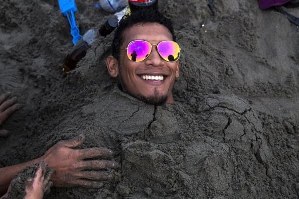 Ngày 16-2, một nam du khách thích thú chôn mình dưới cát, nhưng cũng chính vị trí đó hôm 24-3, bãi biển chỉ còn vỏ sò, vỏ ốc và một chiếc dép bị sóng đánh dạt vào. Ảnh: AP 1