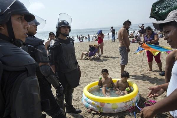 Những nhân viên an ninh ngày 24-3 chỉ còn đi tuần tra trên một bãi biển không một bóng người. Ảnh: AP 1