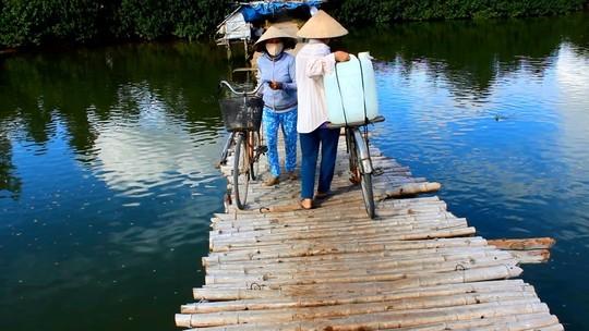 Người dân đi qua cây cầu thô sơ này để qua sông