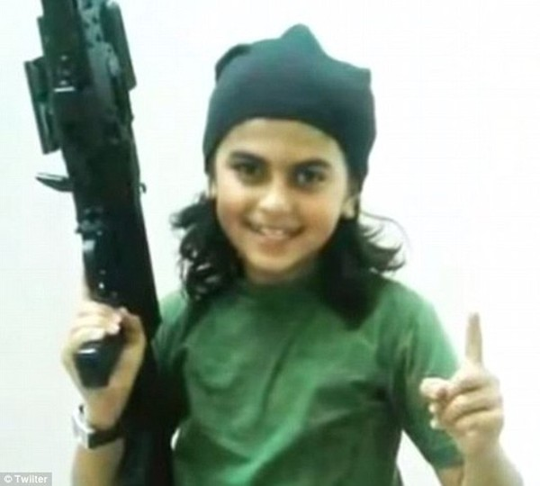 Smiling: Describing the child as ISIS youngest foreign jihadist, chilling photographs taken before his alleged death show him grinning at the camera, wearing military fatigues and brandishing a huge assault rifle