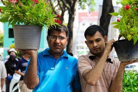Tại khu phố Tây Phạm Ngũ Lão rất nhiều khách nước ngoài cũng thích thú hòa vào dòng người mua hoa và cũng lựa cho mình những chậu hoa nhỏ xinh.