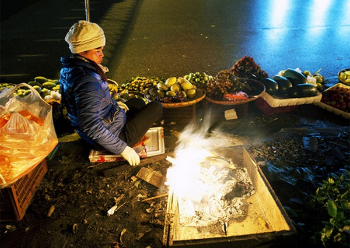 Nhiệt độ xuống thấp về đêm, nhiều người buôn bán phải đốt lửa sưởi ấm. ẢNh: Nguyên Anh.