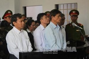 Bị cáo Vũ Việt Hùng (áo xanh bên phải) trước vành móng ngựa. (Ảnh: K' Guih/TTXVN)