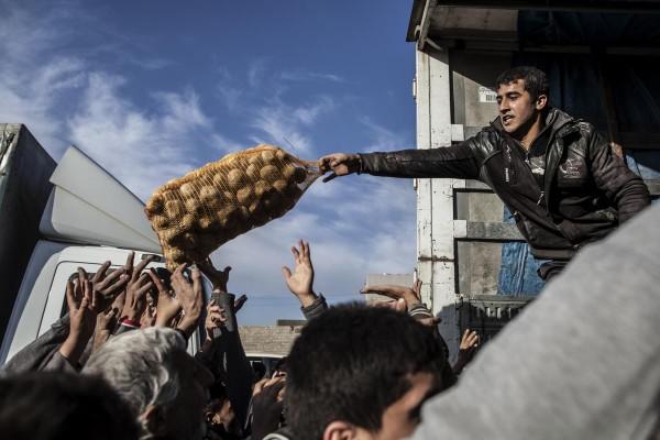 Người dân quận Samah (Mosul) nhận khoai tây cứu trợ ngày 4-12. Ảnh: AP
