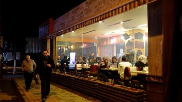 Người dân ăn uống tại nhà hàng ở tây Aleppo (Syria) ngày 2-12. Ảnh: AP