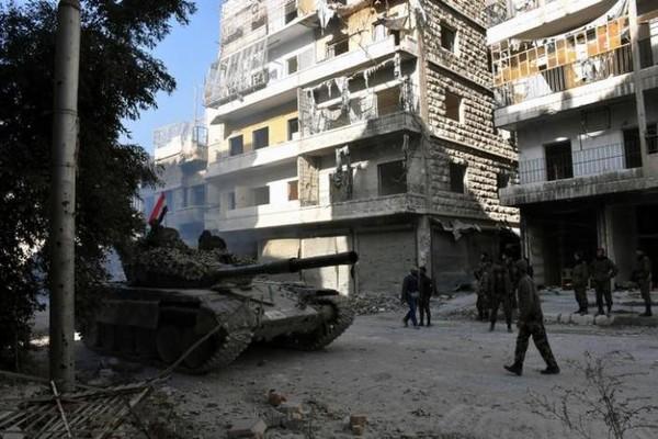 Lính và xe tăng chính phủ Syria ở Aleppo ngày 8-12. Ảnh: REUTERS