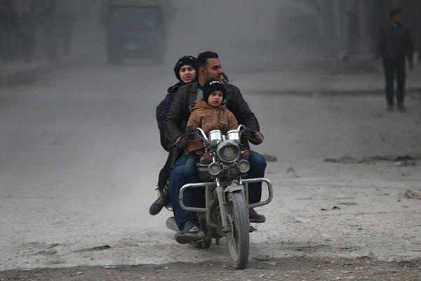Người dân chạy sâu vào trong khu vực phe nổi dậy kiểm soát ở Aleppo ngày 9-12. Ảnh: REUTERS
