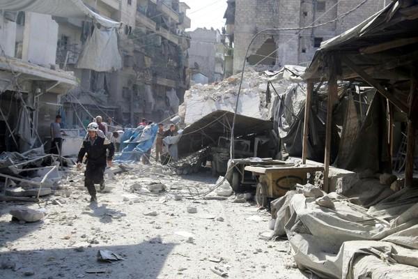 Nhân viên bảo vệ công dân tại một ngôi chợ ở quận al-Fardous (Aleppo) bị không kích ngày 17-10.