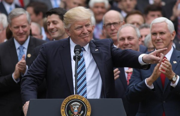 Tổng thống Mỹ Donald Trump (giữa), Phó Tổng thống Mỹ Mike Pence (phải) mừng chiến thắng sau khi Hạ viện thông qua dự luật hủy bỏ Obamacare ngày 4-5. Ảnh: REUTERS