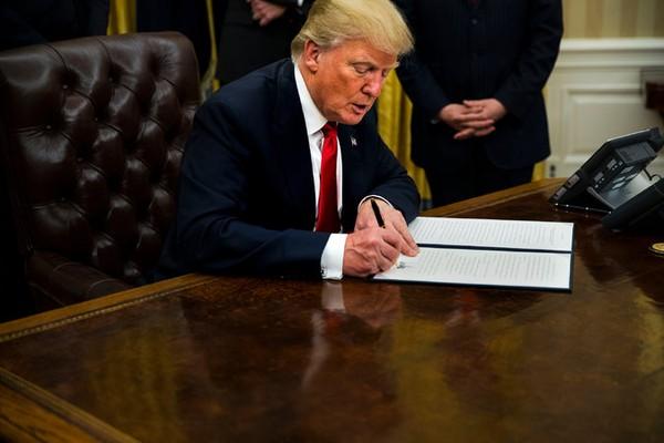 Tổng thống Trump ký sắc lệnh xúc tiến hủy bỏ Obamacare không lâu sau khi nhậm chức. Ảnh: NYT