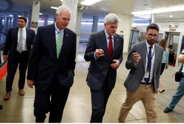 Các thượng nghị sĩ Cộng hòa Bill Cassidy(phải) và Ron Johnson (giữa) trao đổi với báo chí tại tòa nhà Quốc hội ngày 26-9. Ảnh: REUTERS