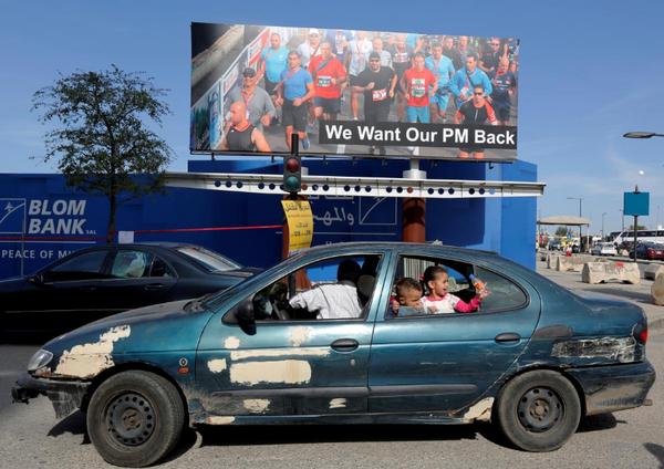 """Áp phích """"Tôi muốn Thủ tướng chúng tôi quay lại"""" được trưng tại thủ đô Beirut (Lebanon) trong ngày chạy bộ hàng năm Beirut Marathon 12-11. Ảnh: REUTERS"""