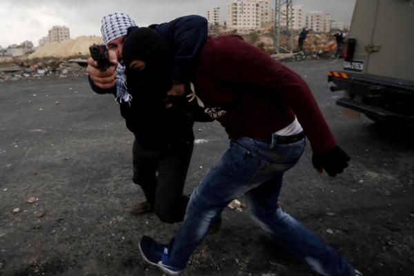 Cảnh sát thường phục Israel giữ một người Palestine trong cuộc xung đột biểu tình ở khu định cư Do Thái Beit El, gần TP Ramallah ở Bờ Tây ngày 13-12-2017, phản đối Mỹ công nhận Jerusalem là thủ đô Israel. Ảnh: REUTERS