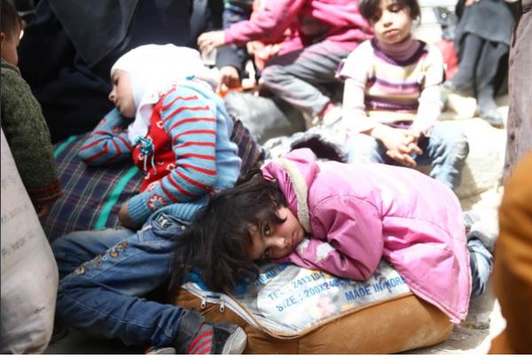 Trẻ em mệt mỏi chờ sơ tán khỏi thị trấn Douma, Đông Ghouta, ngoại ô thủ đô Damacus (Syria) ngày 22-3. Ảnh: REUTERS