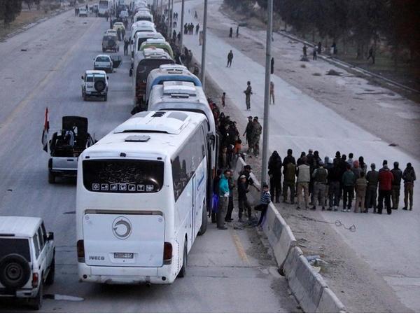 Đoàn xe chở các tay súng nổi dậy và người thân ở thị trấn Harasta, Đông Ghouta, ngoại ô thủ đô Damacus (Syria) ngày 22-3. Ảnh: REUTERS