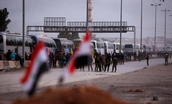 Đoàn xe chở các tay súng nổi dậy và người thân ở thị trấn Harasta, Đông Ghouta, ngoại ô thủ dô Damacus (Syria) ngày 22-3. Ảnh: REUTERS