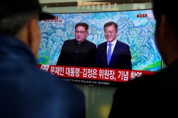 Người dân Seoul (Hàn Quốc) xem bản tin về cuộc gặp thượng đỉnh liên Triều. Tổng thống Hàn Quốc Moon Jae-in (phải) chụp hình chung với lãnh đạo Triều Tiên Kim Jong-un trước bức tranh núi Kim Cương ở Triều Tiên được treo trong Nhà Hòa Bình. Ảnh: REUTERS