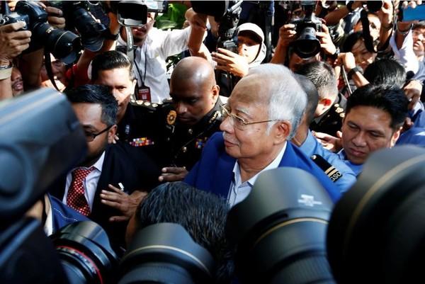 Cựu Thủ tướng Malaysia Najib Razak len lỏi trong hàng rào phóng viên khi đến trình diện và chịu thẩm vấn tại Ủy ban Chống tham nhũng ở Putrajaya (Malaysia) sáng 22-5. Ảnh: REUTERS