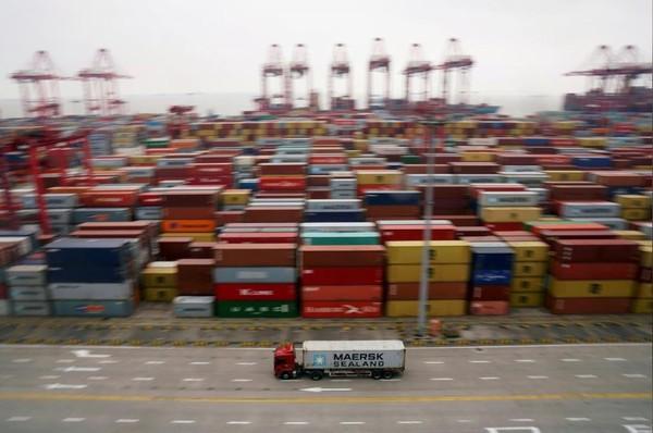 Xe tải và container hàng tại cảng nước sâu Yangshan ở Thượng Hải (Trung Quốc), ngày 24-4. Ảnh: REUTERS