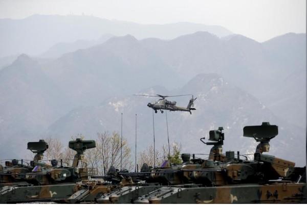 Trực thăng quân sự AH-64 của Mỹ bay phía trên xe bọc thép trong một cuộc tập trận bắn đạn thật Mỹ-Hàn, diễn ra ở TP Pocheon, tỉnh Gyeonggi (Hàn Quốc) - gần khu phi quân sự liên Triều ngày 21-4-2017. Ảnh: REUTERS