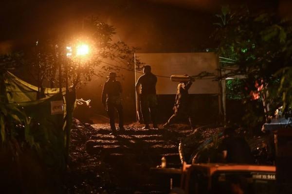 Lực lượng cứu hộ mang bình oxy vào hang động Tham Luang cung cấp cho các thành viên đội bóng nhí, khuya 2-7. Ảnh: GETTY IMAGES