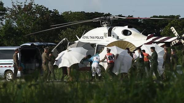 Cảnh sát và quân đội Thái di chuyển một thành viên đội bóng nhí từ trực thăng xuống xe cứu thương tại một căn cứ quân sự ở Chiang Rai ngày 9-7. Ảnh: AFP