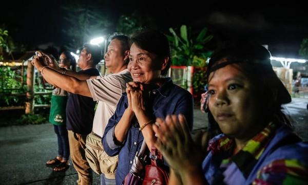 Người dân mừng vui theo dõi xe cứu thương chở các cậu bé được cứu ra khỏi hang động về bệnh viện để được chăm sóc sức khỏe, khuya 8-7. Ảnh: GETTY IMAGES