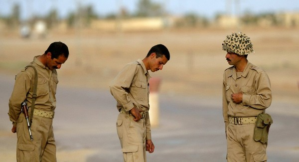 Các thành viên của nhóm đối lập Mujahideen-e Khalq đang trấn giữ một con đường dẫn tới trụ sở chính của nhóm tại TP Baqubah, thủ phủ Lãnh thổ Diyala (Iraq) tháng 5-2003. Ảnh: AP