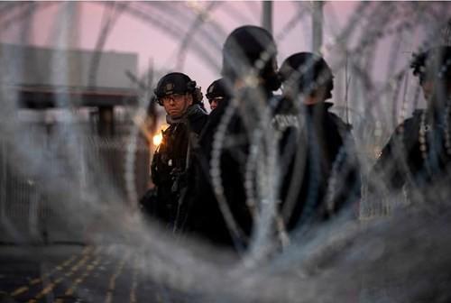Lực lượng phản ứng đặc biệt của Cơ quan Hải quan và Bảo vệ biên giới Mỹ bên hàng rào thép gai tại cửa khẩu San Ysidro, TP San Diego, bang California (Mỹ) giáp Mexico ngày 19-11. Ảnh: REUTERS