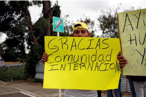 """Một người dân Venezuela mang biểu ngữ có dòng chữ: """"Cám ơn cộng đồng quốc tế"""" đứng gần một nhà kho nơi chứa hàng cứu trợ nhân đạo cho Venezuela, gần cây cầu Tienditas nối biên giới Colombia và Venezuela ở tỉnh Cucuta (Colombia) ngày 8-2. Ảnh: REUTERS"""