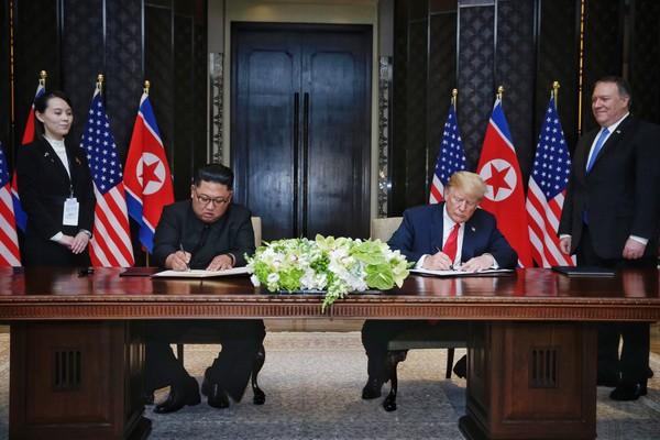 Tổng thống Mỹ Donald Trump (phải) và lãnh đạo Triều Tiên Kim Jong-un ký tuyên bố chung trong cuộc gặp thượng đỉnh đầu tiên ở khách sạn Capella (Singapore) ngày 12-6-2018. Ảnh: AFP