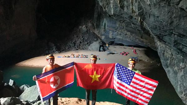Một nhóm thám hiểm hang động Sơn Đoòng ở tỉnh Quảng Bình giơ cao các lá cờ Triều Tiên, Việt Nam, Mỹ (từ trái sang), chào mừng sự kiện cuộc gặp thượng đỉnh Mỹ-Triều sắp diễn ra tại Hà Nội vào ngày 27 và 28-2. Ảnh: AP