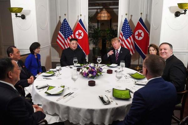 Tổng thống Donald Trump cùng phái đoàn Mỹ (phải) và lãnh đạo Kim Jong-un cùng phái đoàn Triều Tiên (trái) trong bữa ăn tối qua 27-2. Ảnh: CNN