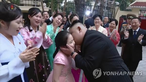 Lãnh đạo Triều Tiên Kim Jong-un hôn má một cậu bé trong lễ đón ông đến thăm Đại sứ quán Triều Tiên ở Hà Nội chiều 27-2. Ảnh: YONHAP chụp lại từ màn hình đài truyền hình trung ương Triều Tiên KCTV