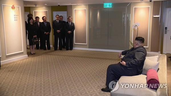 Các quan chức Triều Tiên đứng nghe chỉ đạo từ lãnh đạo Triều Tiên Kim Jong-un (ngồi, phải) tại khách sạn Melia ở Hà Nội. Ảnh: YONHAP chụp lại từ màn hình đài truyền hình trung ương Triều Tiên KCTV