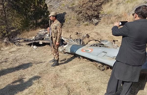 Một binh sĩ Pakistan đứng gác gần xác chiếc máy bay của Ấn Độ bị phía Pakistan bắn rơi hồi tháng 2. Ảnh: AP