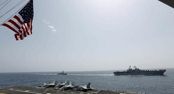 Tàu đổ bộ tấn công USS Kearsarge (phải) và tàu khu trục USS Bainbridge (trái) trang bị tên lửa dẫn đường di chuyển trên biển Ả Rập ngày 17-5. AP đưa hình ảnh được chụp từ tàu sân bay USS Abraham Lincoln.