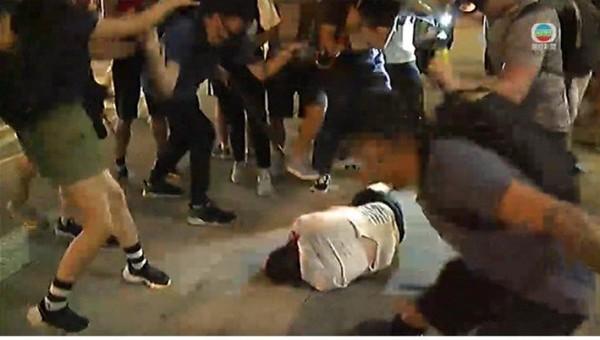 Một người đàn ông bị đánh nằm bất tỉnh trên đường với đầu đầy máu tối 15-9. Ảnh: SCMP
