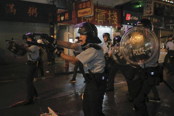 Cảnh sát chĩa súng vào người biểu tình trong một cuối tuần biểu tình ở Hong Kong hồi tháng 8. Ảnh: AP